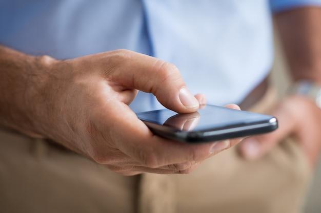 タッチスクリーンのスマートフォンを持っている人の手のクローズアップ