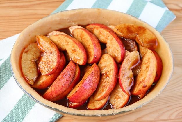 自家製アップルパイを焼く前に新鮮な混合充填物でパイプレートのクローズアップ