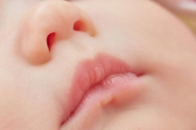 핑크 아기 입술과 코의 근접 촬영입니다. 부드러운 피부.
