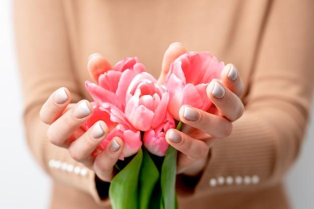핑크 튤립의 근접 촬영 젊은 여자의 손에 새싹. 여성의 손에 핑크 꽃