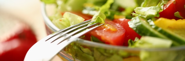 Крупный план тарелки с салатом и вилкой зелени и помидоров. концепция здорового питания здорового образа жизни