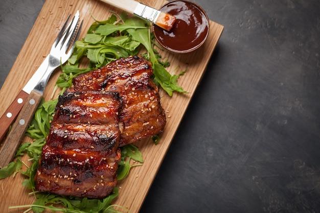 Крупным планом свиные ребрышки на гриле с соусом барбекю.