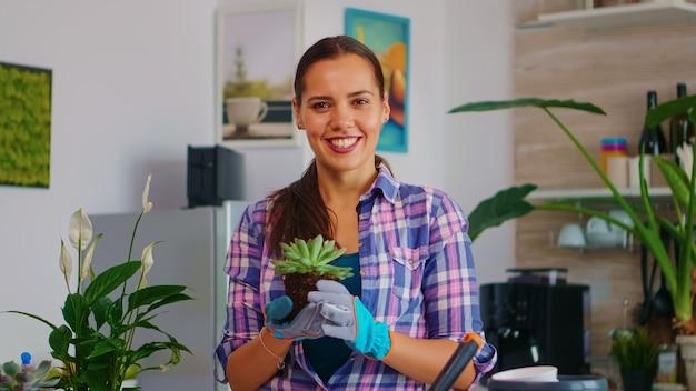 웃 고 꽃을 들고 초상화 여자의 근접 촬영입니다. 꽃집은 집 장식을 위해 삽, 장갑, 비옥한 토양, 꽃을 사용하여 세라믹 냄비에 꽃을 심습니다.
