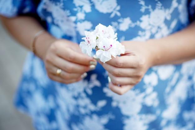 妊娠中の女性の花を押しながら彼女の腹に触れるのクローズアップ