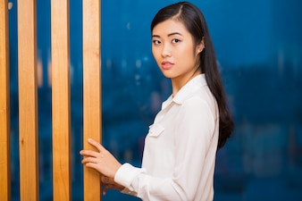 Closeup of Pretty Asian Lady at Wooden Partition