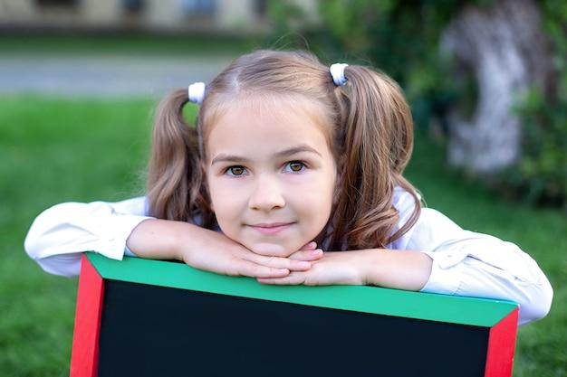 長い髪のかなりかわいい女の子のクローズアップ。彼女の頭に2つのポニーテールを持つ少女は、学校の近くの公園で黒板にもたれています。