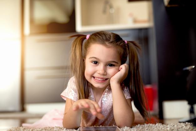 タブで遊ぶ2つのポニーテールでかわいい女の子のクローズアップ