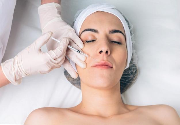 클리닉 치료의 일부처럼 얼굴에 화장품 주사를 맞는 예쁜 여성의 클로즈업. 의학, 건강 관리 및 미용 개념입니다.