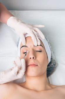 Крупным планом красивая женщина получает косметические инъекции в лицо, как часть лечения в клинике. концепция медицины, здравоохранения и красоты.