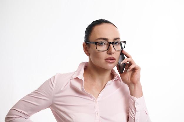 携帯電話で話し、カメラを見て、コピースペースと白い背景で隔離のかなり若いビジネス女性のクローズアップ。