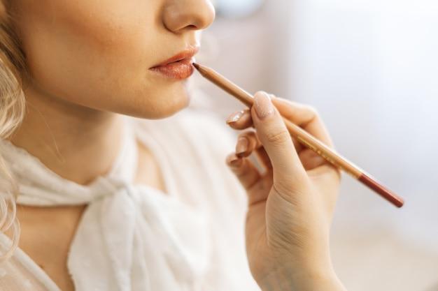 リップペンシルでメイクアップ若い女性の唇を作るプロのメイクアップアーティストのクローズアップ
