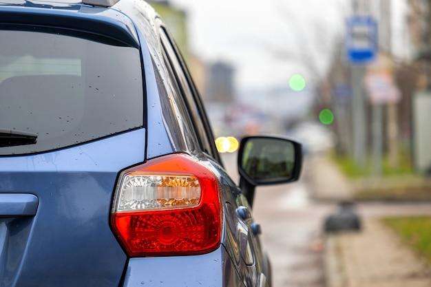 도시 거리 쪽에 주차된 깨끗한 새 차의 후면 헤드라이트를 닫습니다.