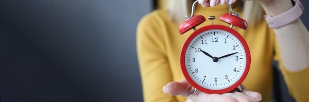 女性の手に赤い目覚まし時計のクローズアップ