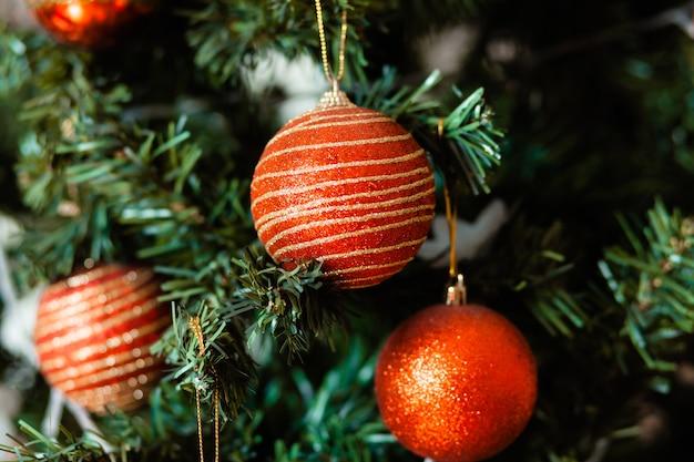 Крупный план красной безделушки, свисающей с украшенной рождественской елки. эффект ретро-фильтра.
