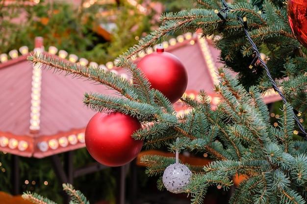 Крупным планом красные елочные шары и гирлянда на ветвях натуральной новогодней елки