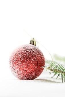 雪の上の赤いクリスマス飾りのクローズアップ。