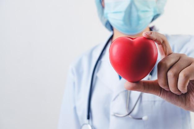 白い背景の上の聴診器と医師の手で赤いハートのクローズアップ。医療関係者とカーディオプラクティショナーの概念。心臓の寄付とライフレスキューヘルスケアのテーマ。