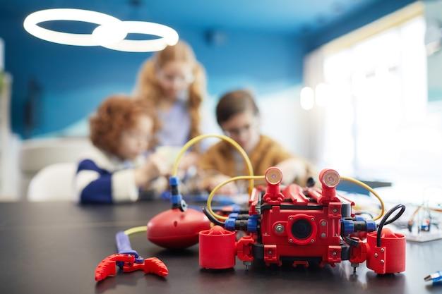 Крупным планом красный робот-машина на столе в инженерном классе с детьми в фоновом режиме, копией пространства