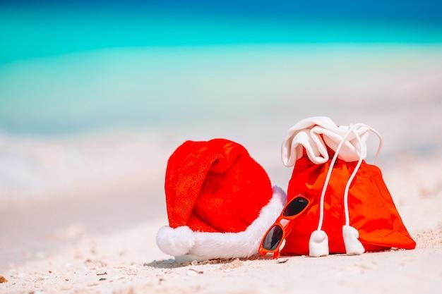 ビーチで赤いサンタバッグとサンタクロースの帽子のクローズアップ。クリスマス旅行休暇と旅行cupriseの概念。白い熱帯のビーチでサンタ帽子とビーチアクセサリー