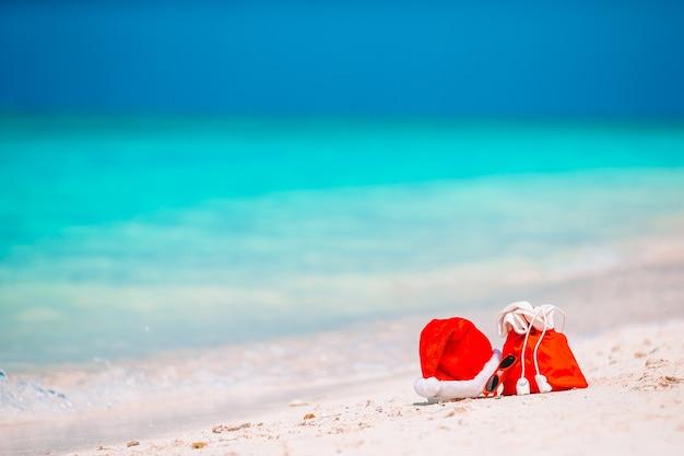 ビーチで赤いサンタバッグとサンタクロースの帽子のクローズアップ