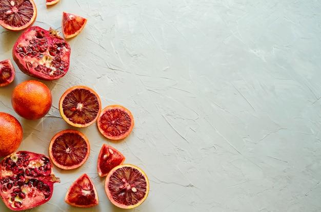 빨간 시칠리아 혈액 (피 묻은) 오렌지의 근접 촬영-잘라 내기, 슬라이스, 잘 익은 맛있는 copyspace, 회색 시멘트 배경