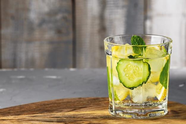 灰色の木製テーブルの上のガラスカップにキュウリとレモンとさわやかな水のクローズアップ。デトックスコンセプト