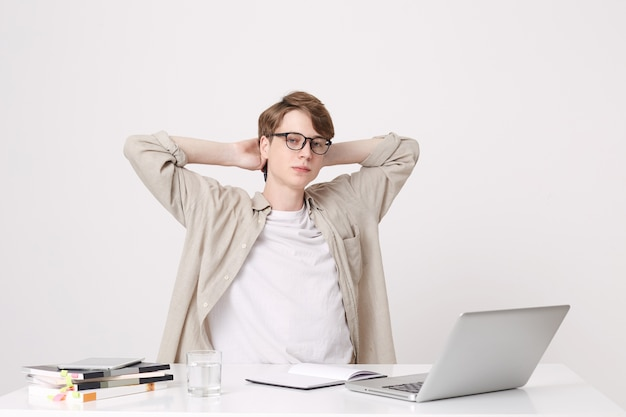 リラックスした自信を持って若い男の学生のクローズアップは、白い壁に隔離されたラップトップコンピューターとノートブックとテーブルで頭上に手を置いて座っているベージュのシャツと眼鏡を身に着けています