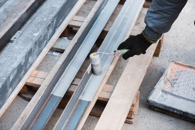 Крупным планом ремонтник в униформе, профессиональный строитель, работающий с использованием строительного оборудования. процесс строительства, ремонт квартир, ремонт, строительство. окрашивание, замер, подготовка основы.