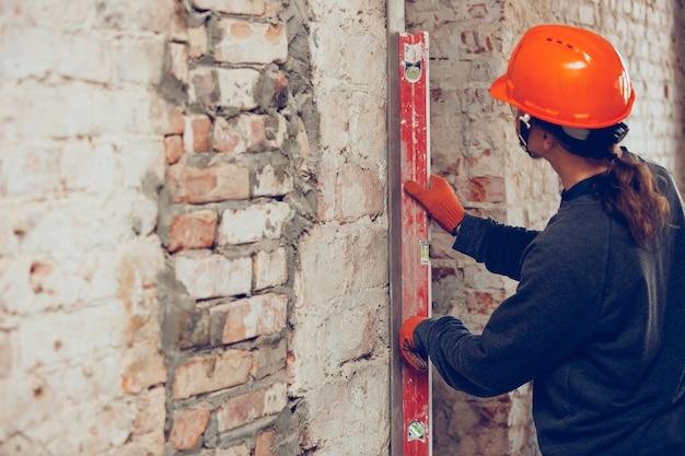 Крупным планом ремонтник в униформе, профессиональный строитель, работающий с использованием строительного оборудования. процесс строительства, ремонт квартир, ремонт, строительство. распиловка, соединение, резка, подготовка.