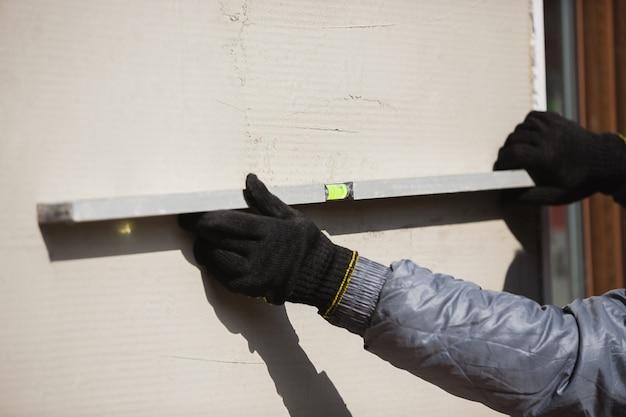 Крупный план ремонтника в униформе профессионального строителя, работающего с использованием конструкции