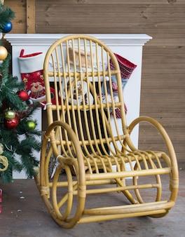 선물용 양말과 크리스마스 트리가 있는 벽난로 옆 흔들의자 클로즈업