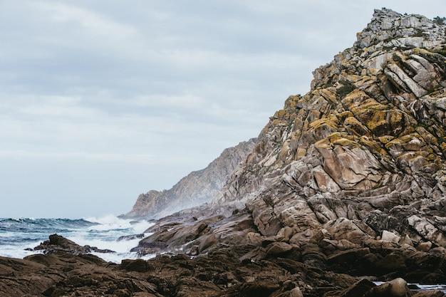 낮에는 흐린 하늘 아래 바다로 둘러싸인 바위의 근접 촬영