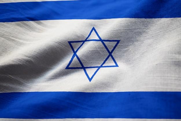 Макрофотография взломанного израильского флага, израильский флаг, дующий в ветру