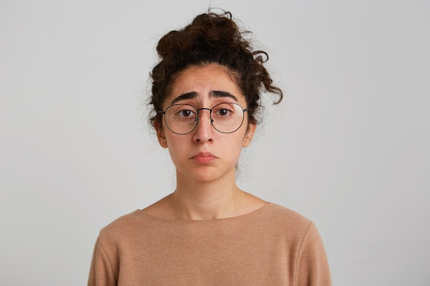 巻き毛の悲しい落ち込んでいるグルジアの若い女性のクローズアップはベージュのプルオーバーを身に着けており、眼鏡は白い壁の上に孤立して動揺し、失望していると感じています