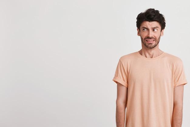 剛毛の悲しい不満の若い男のクローズアップは、桃のtシャツを着て不満を感じ、白で隔離された彼の顔をしかめっ面