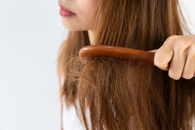 Крупный план грустной молодой азиатской девушки чистит ее поврежденные волосы. изолированные на белом фоне с копией пространства