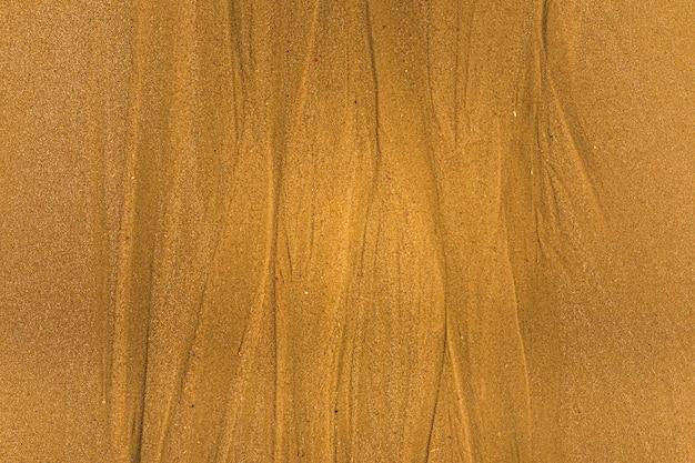 ビーチのフルフレームテクスチャの背景に潮の道と貝殻と砂のクローズアップ