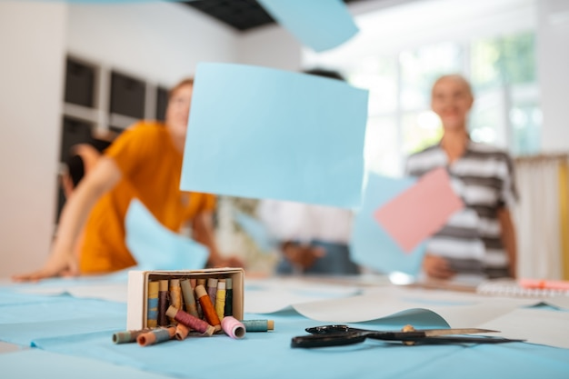 はさみ、色のついた糸の箱、その他の裁縫道具がカッティングテーブルの上に横たわっているクローズアップ