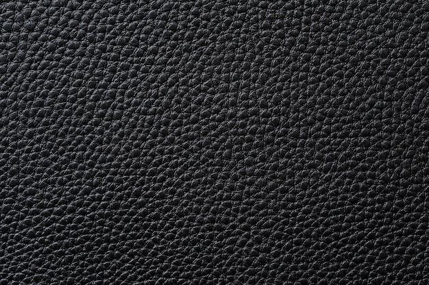 背景のシームレスな黒革のテクスチャのクローズアップ