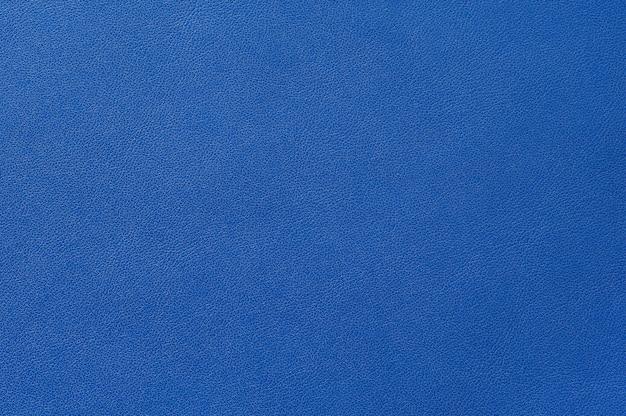 背景のシームレスな青い革のテクスチャのクローズアップ