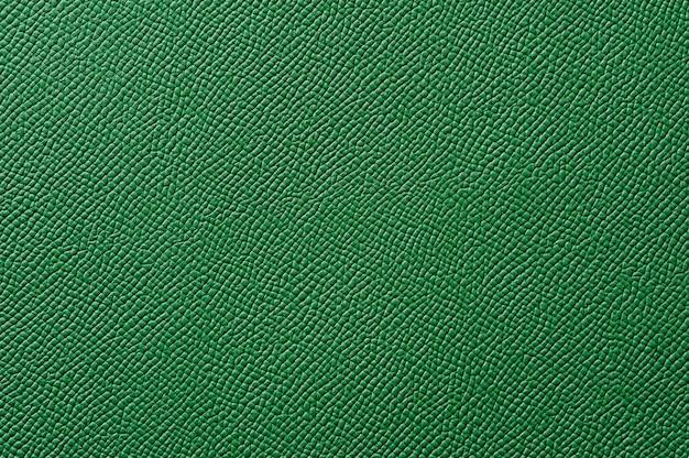 背景のシームレスな緑の革のテクスチャのクローズアップ