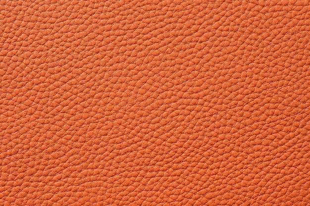 背景のシームレスなオレンジ色の革のテクスチャのクローズアップ