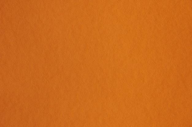 배경 또는 삽화에 대한 원활한 주황색 종이 질감의 근접 촬영
