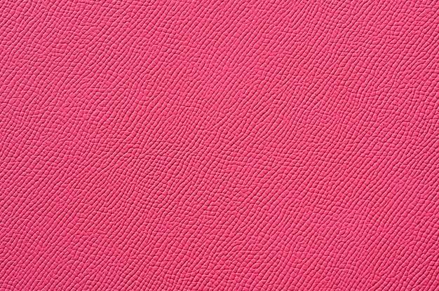 背景のシームレスなピンクの革のテクスチャのクローズアップ
