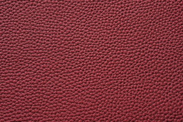 背景のシームレスな赤い革のテクスチャのクローズアップ