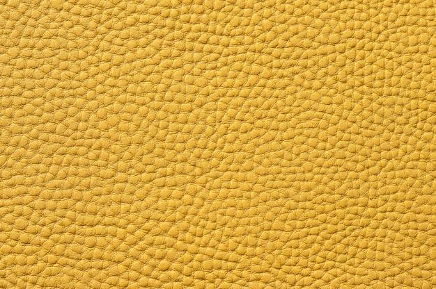 背景のシームレスな黄色の革のテクスチャのクローズアップ