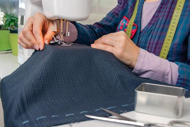 ミシンで衣料品を扱う針子の手のクローズアップ