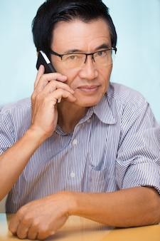 Closeup of Senior Asian Man Calling on Phone