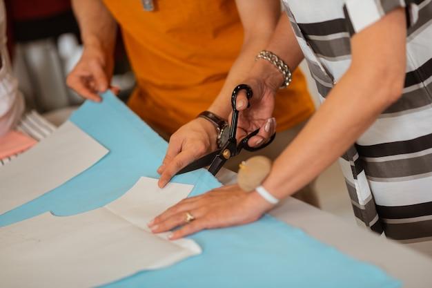 はさみを使用してシニア女性の仕立て屋の手のクローズアップ