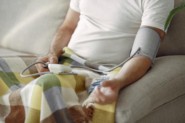 圧力を測定する70〜75歳のシニア男性のクローズアップ。彼女の血圧を測定する男。健康とケア。